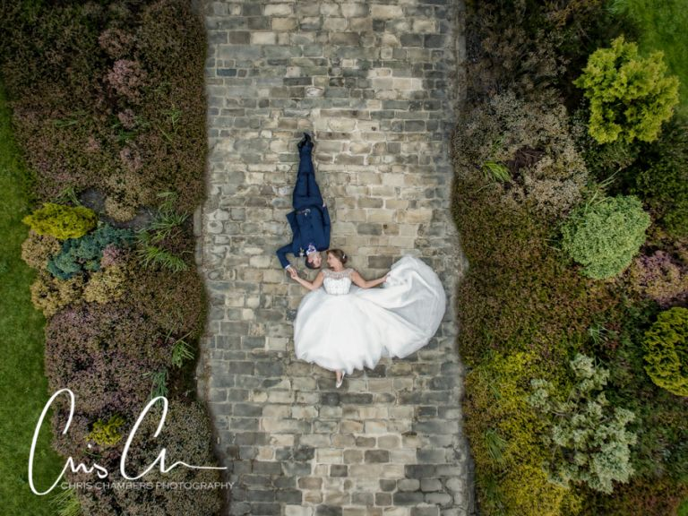 Waterton Park Hotel Wedding Photography in West Yorkshire, Bride and groom lay on the path for a drone wedding photograph