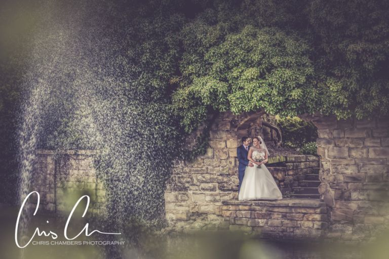 Bride and groom stand in the archway overlooking the lake on their wedding day. Waterton Park Hotel weddings award winning wedding photographer