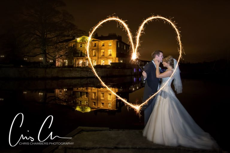 Walton Hall wedding photography in Yorkshire with bride and groom and sparklers at night with a reflection of Walton Hall behind them