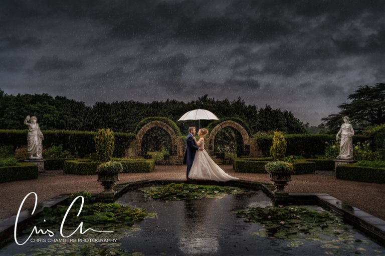 Bride and groom in the rain at Allerton Castle, North Yorkshire wedding venue potographed by recommended photographer Chris Chambers.