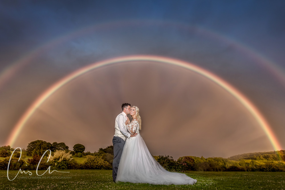 Bride and groom with a double rainbow at a wedding