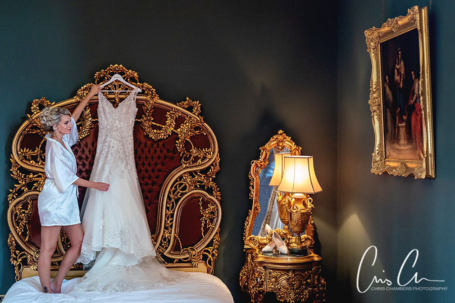 Yorkshire wedding photographer at Allerton Castle. Wedding dress hanging in the bedroom at Allerton Castle