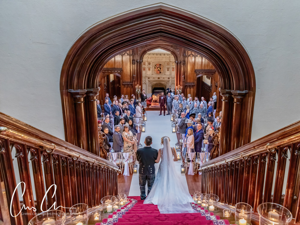 Bridal entrance into the wedding ceremony down the grand staircase at Allerton Castle North Yorkshire.