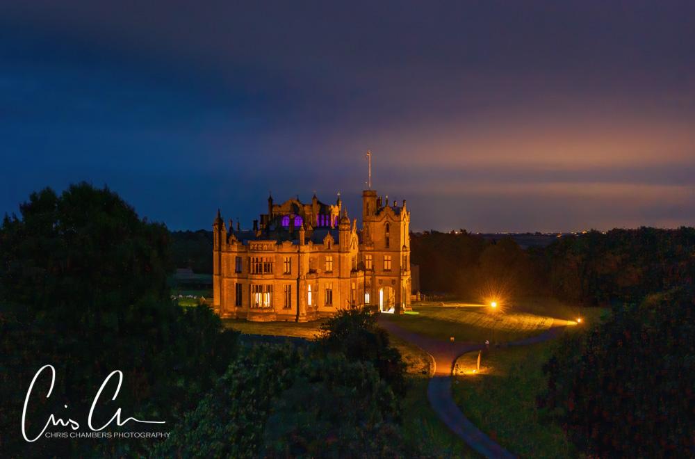Allerton Castle at dusk, floodlights illuminate the stunning Yorkshire Castle wedding venue. Photography from award winning wedding photographer Chris Chambers