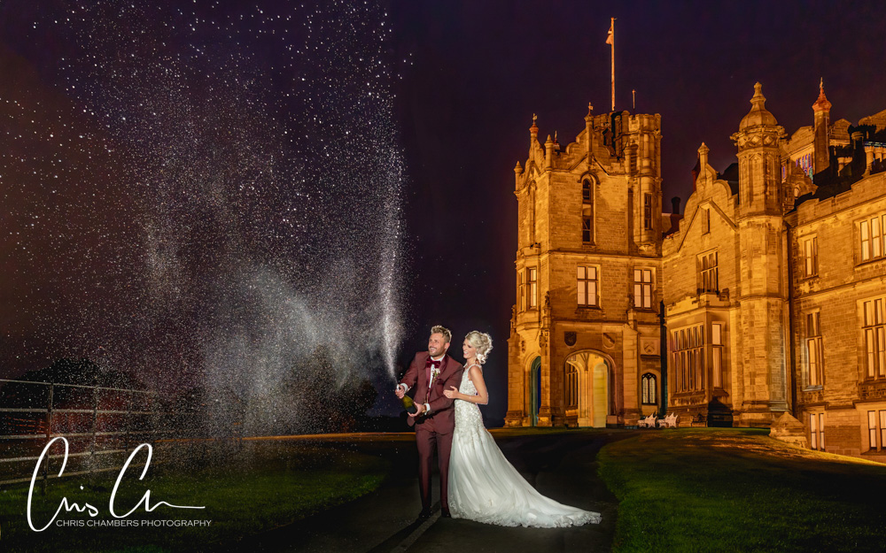 Bride and groom spray champagne on their wedding day at Allerton Castle North yorkshire