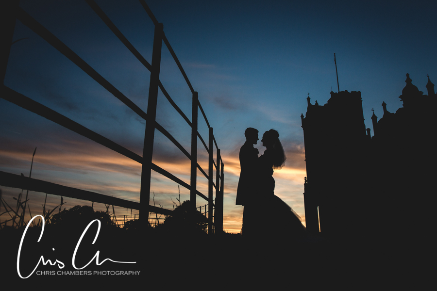 Sunset at Allerton Castle North Yorkshire. Bride and groom silhouetted against the sunset with the castle in the background