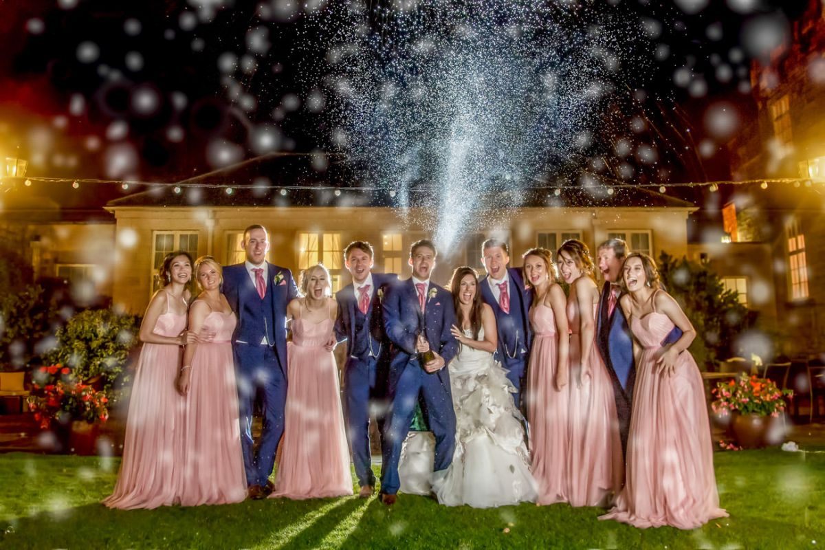 spraying champagne wedding photograph at Hazlewood Castle near York