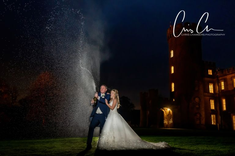 Bride and groom spray champagne in the evening of their wedding day.  Swinton Park Wedding Photograph