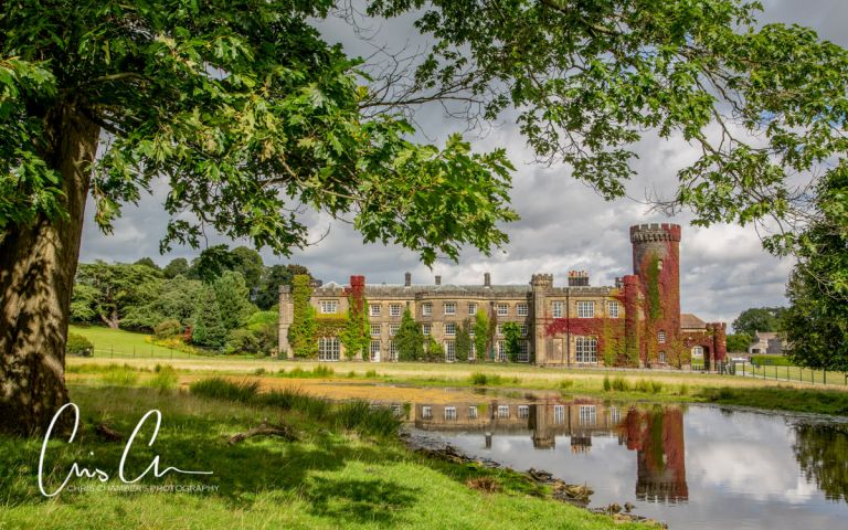 Yorkshire wedding venue, photograph of Swinton Park with reflection in the lake and seasonal red ivy. Swinton Park Wedding Photograph